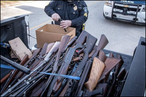 A variety of firearms are impounded in this photo including Mauser bolt action rifles, lever-action Winchesters, and a Browning Auto 5 semi auto shotgun.